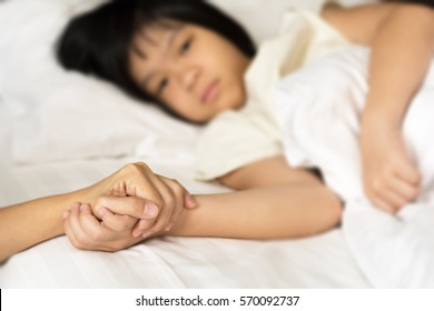Hands of mother and sick asian daughter holding together in hospital or home to give encouragement.Female student sleep on white bed cannot go to school as illness with caregiver.Healthcare medical