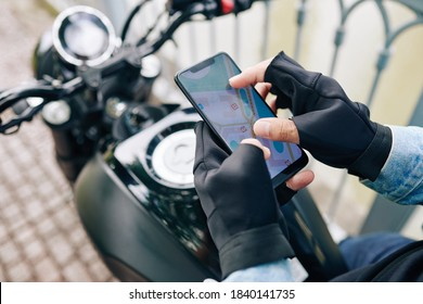 Hands of motorcyclist zooming in map on smartphone screen before riding to destination point