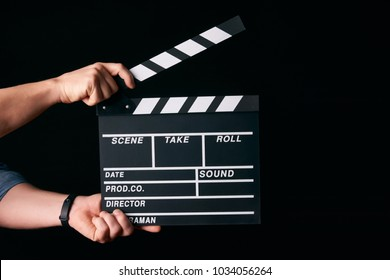 Hands with a movie clapperboard isolated on black background with copy space, close-up. Wooden clapper board as cinema and movie time concept