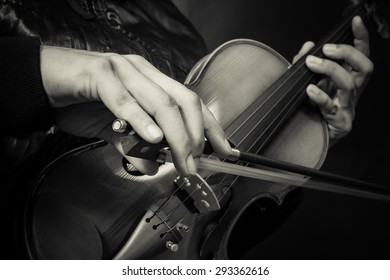 hands of musician in black jacket playing classical violin, vintage filter