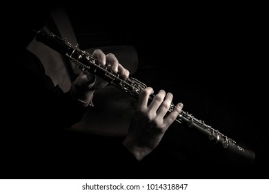 Hands of a musician on bassoon keys on a black background