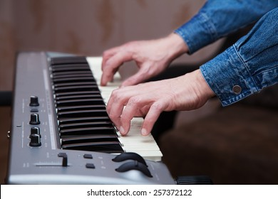 hands of the musician on the keyboard synthesizer