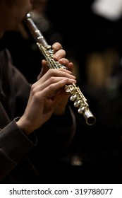 Hands of musician playing a flute in dark colors