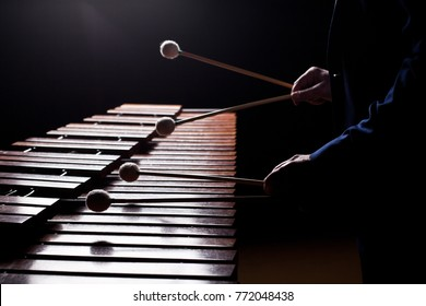 Die Hände eines Musikers, der die Marimba in dunklen Tönen spielt