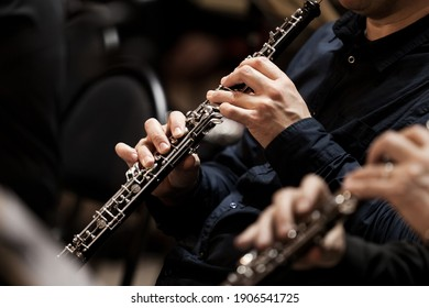 Hands of a musician playing the oboe in an orchestra