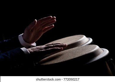 Hands of a musician playing on bongs in dark tones closeup