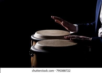 Hände eines Musikers, der auf Beinen in dunklen Tönen spielt