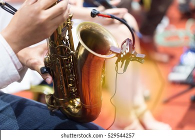 Hands of musicians who are blowing the saxophone.