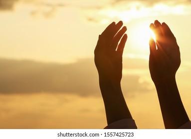 Hands of Muslim woman praying outdoors at sunset