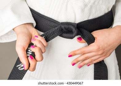 Hands with nail polish of a girl with a black belt in martial arts, close up