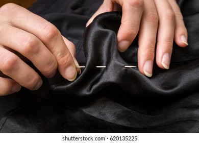 Hands with a needle and thread sewing clothes. Handmade. Womanly hobby.