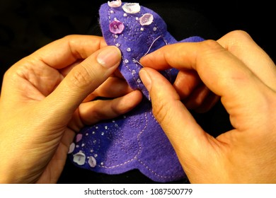 Hands of needlewoman are beaded with purple wings made of cloth. Beautiful bijouterie made by hand. Skillful hands and skill. Work sewing needle and beads.