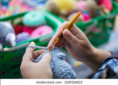Hands of a needlewoman crochet. Female fingers knit a toy. Handmade craft.