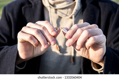 Hands of nervous smoker man with chewed nails breaking cigarette on the half when he decided to quit bad habit of smoking selective focus close up