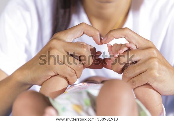 Hands of newborn baby in mother hands