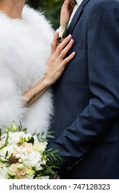 Hands of the newlyweds with a bouquet of flowers