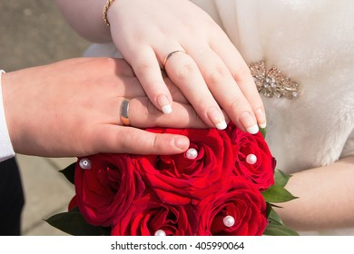 Hands newlyweds on a bouquet