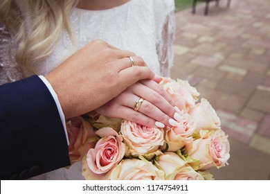 The hands of newlyweds with rings on the background of bouquet. The symbol of a new family. Marriage, wedding, wedding gold rings