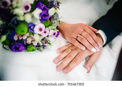 Hands are newlyweds with wedding rings. Close up. On the background of a wedding bouquet of flowers. Bride Manicure. groom