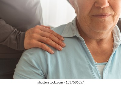 The hands of a nurse support and help an elderly woman. Mature people.