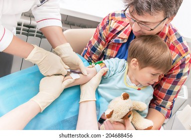 Hands of nurses is collecting a blood from a vein from the patient (kid) in the hospital. Child is fearing (scaring) test of blood. Boy with toy and father are seating in the clinic. Medical concept.