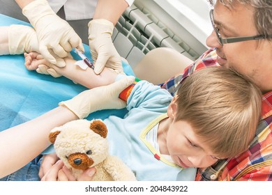 Hands of nurses is collecting a blood from a vein from the patient (kid). Child is fearing (scaring) test (analysis). Boy with toy and his father are in the clinic. Caucasian models. Medical concept.