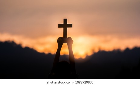 hands off children holding christian cross with light sunset.