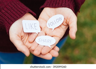 Hands offering speech bubbles with social media concepts.