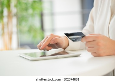 Hands of an office woman typing keyboard with credit card
