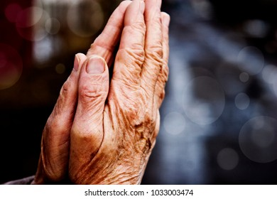 Hands of the old grandmother in prayer on a light background