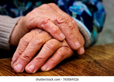 Hands of an old grandmother with wrinkles on a wooden table close-up