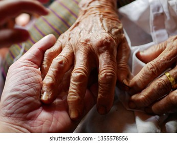 Hands of an old hard working woman on a hand of a younger man - care for elderly people