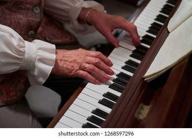 hands of an old lady in festive dress playing the piano (sheet music with blank pages for own notes or text)
