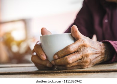 Hands of old man holding cup of coffee on the wood table.vintage tone