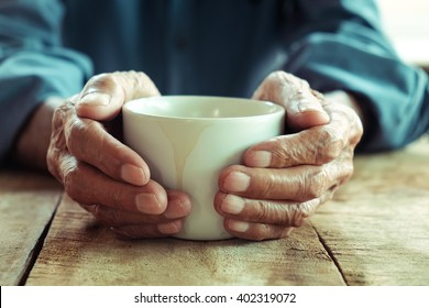 Hands of old man holding cup of coffee.vintage tone