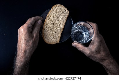 Hands of old man holding a glass of water node black table with a piece of rye bread. The social problem of malnutrition pensioners and low-income segments of society.