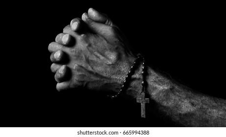 Hands of an old man holding a rosary during praying