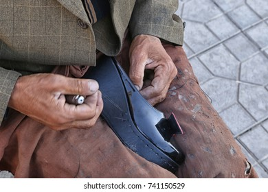 hands of an old man sewing shoes close-ups