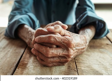 Hands of an old man with wrinkled and wrinkles on the wood table