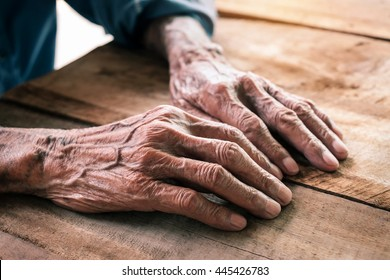 Hands of an old man with wrinkled and wrinkles on the wood table.vintage effect