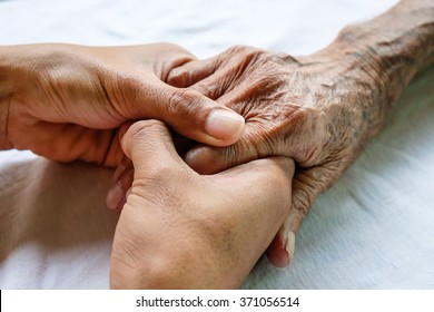 Hands of the old man and a young man on a white bed in a hospital.
