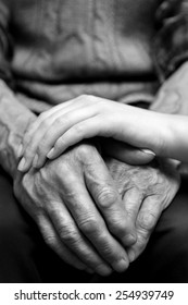 Hands of the old man and a young woman. Black and white.