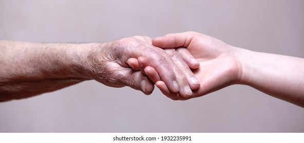Hands of the old man and a young woman.Helping hands.