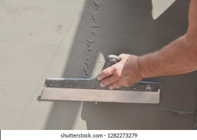Hands of an old manual worker with wall plastering tools renovating house. Plasterer renovating outdoor walls and corners with spatula and plaster. Wall insulation. Construction finishing works