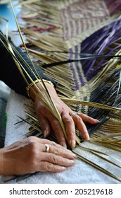 Hands of an old Maori woman from New Zealand weaving a traditional Polynesian woven artwork.
