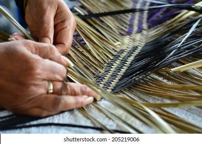 Hands of an old Maori woman weaving a traditional Maori woven artwork.