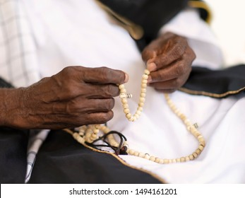 Hands of an old Muslim man holding a rosary (eighty years old)