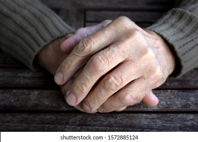 Hands of old senior man with wrinkled palm on wooden table. Vintage tone, close up