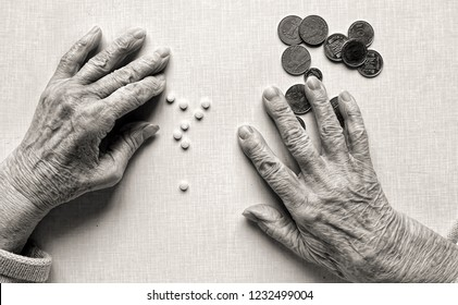 Hands of old woman, counting money (Ukrainian coins). Ampules medicine with syringe and pills lying on the table. Old age, poverty and health concept