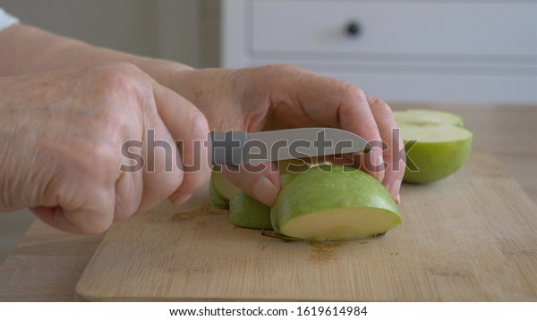 Hands of an old woman is cutting green apple. Closeup at hands